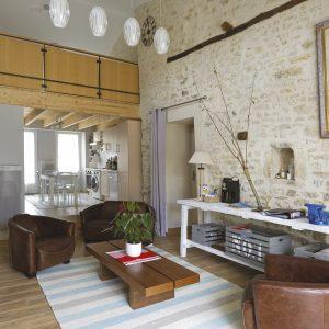 Gite La Grange : le salon et le beau mur de pierre